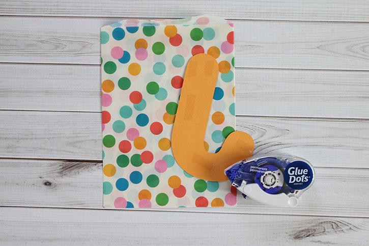 monogrammed-treat-bags-gluing-letter-to-bag.jpg