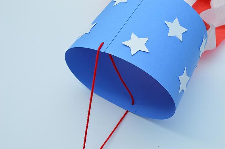 glue-dots-kids-craft-patriotic-windsock-adding-yarn.jpg