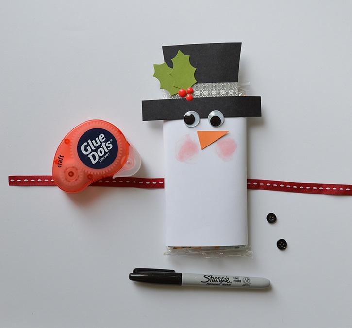 glue-dots-snowman-popcorn-sleeve-adding-face-embellishments.jpg