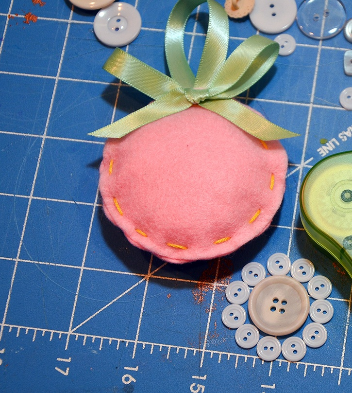 glue-dots-felt-ornament-set-stuffed-with-ribbon-buttons-laid-out.jpg